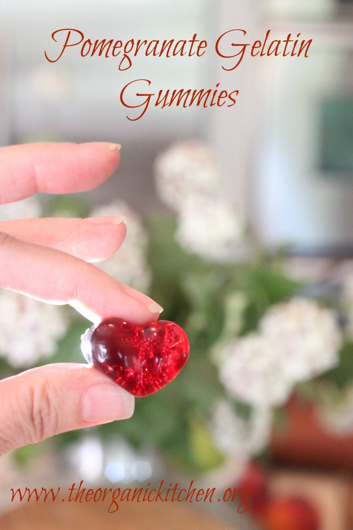 Tow fingers holding bright red Pomegranate Gelatin Gummies