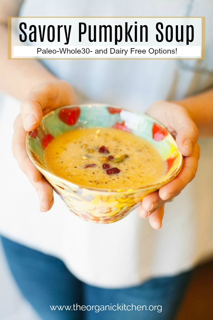 A female's hands holding a colorful bowl of Savory Pumpkin Soup with a dairy free option