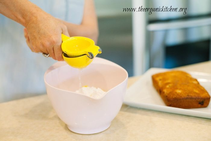 Two hands squeezing lemon juice into a pink bowl in preparation to make Lemon Vanilla Raspberry Cake