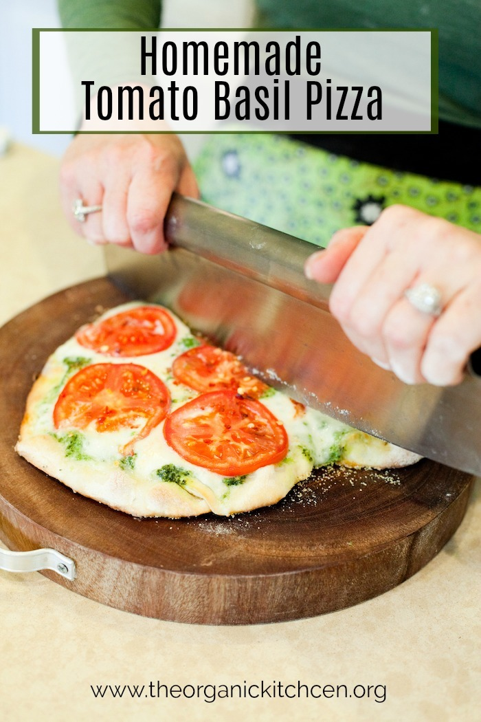 A woman's hands using a pizza cutter to slice a Fresh Tomato Basil Pizza