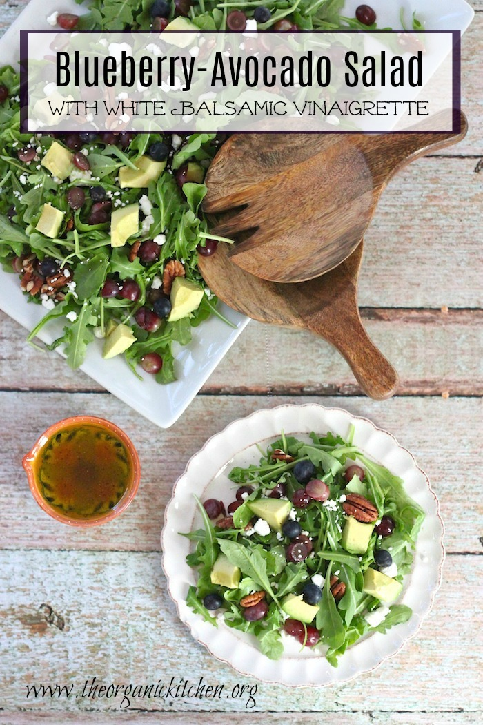 Blueberry and Avocado Salad on a white plate and white platter with wooden serving utensils