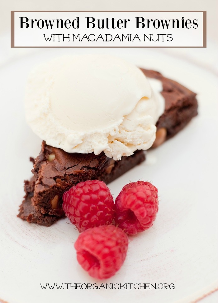 Browned Butter Brownies with Macadamia Nuts topped with ice cream and raspberries on a white surface