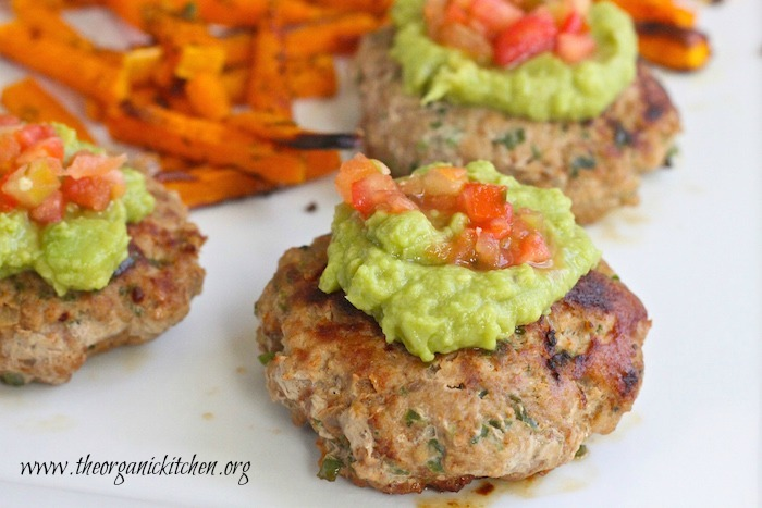 A close up of Jalapeño Turkey Burgers with guacamole and pice de gallo