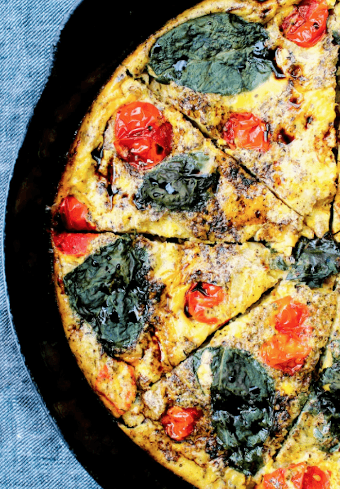 A breakfast frittata in black cast iron pan on blue fabric, one of 12 Healthy, Delicious (Whole 30) Breakfast Recipes!