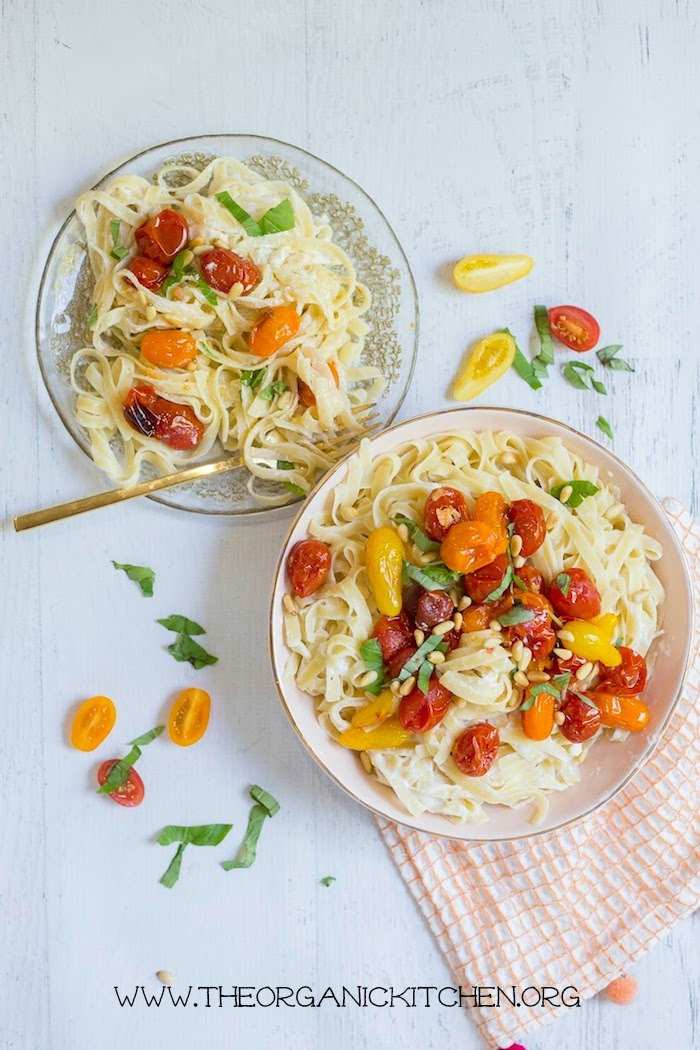 A bowl and plate overflowing with Pasta with Blistered Tomatoes and Ricotta on a white background