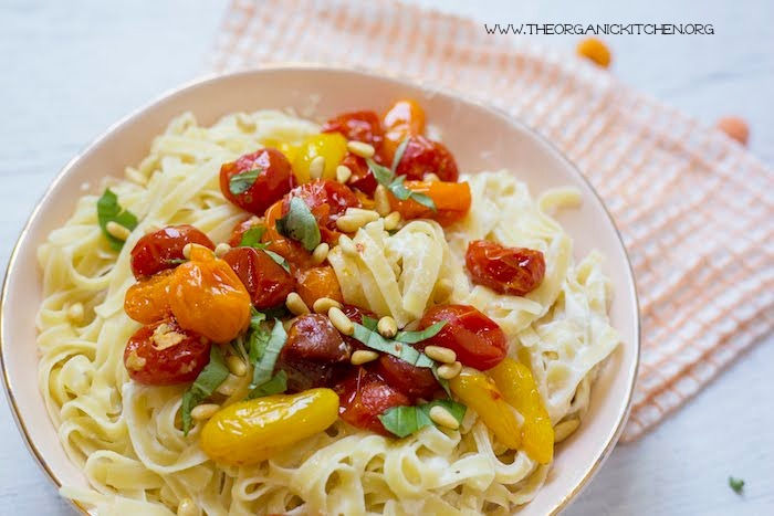 A close up og Pasta with Blistered Tomatoes and Ricotta in light orange bowl with orange and white dish towel