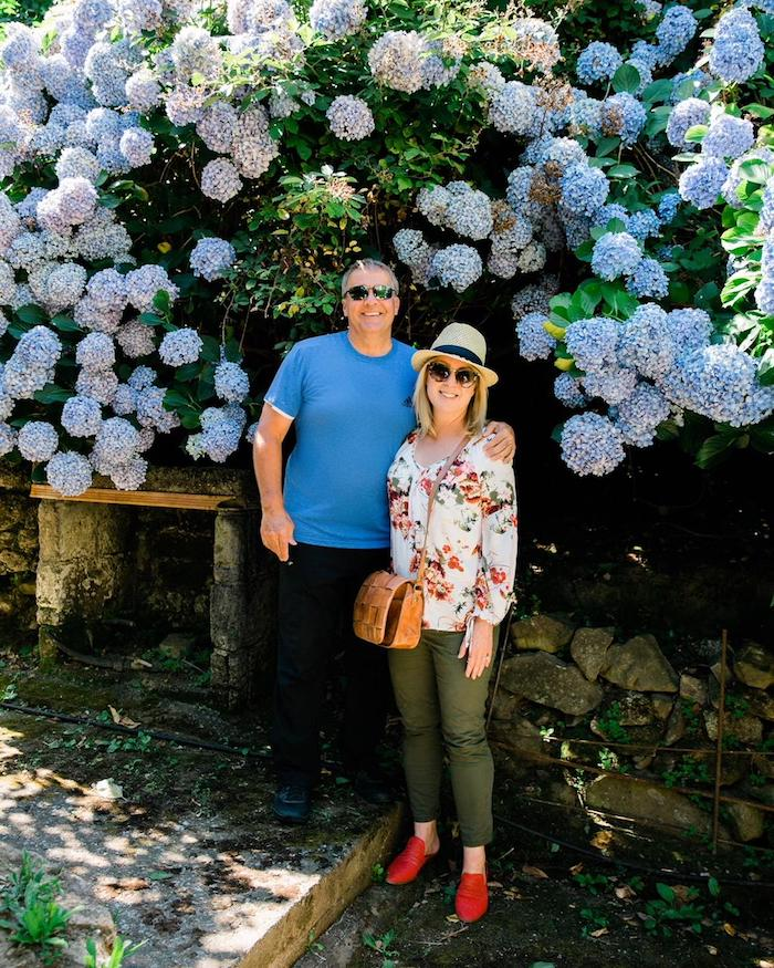 A couple standing in front of huge hydrangea bushes with periwinkle blue flowers  on the Island of Capri