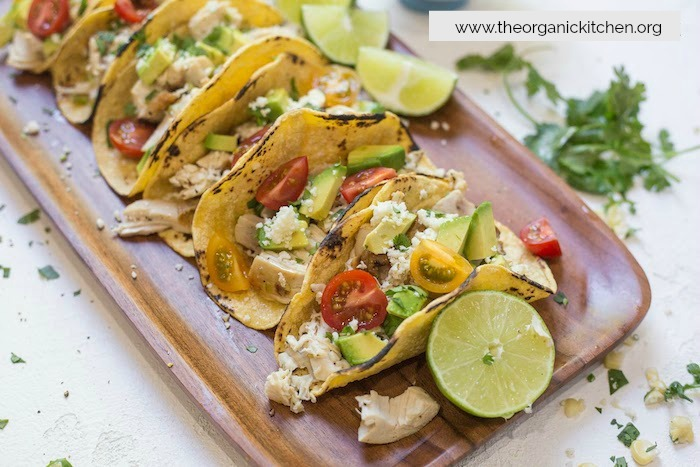 Easy Garlic Lime Chicken Tacos with Lime Crema garnished with lime wedges and cilantro