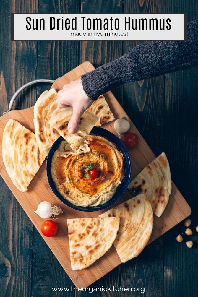 A woman's hand dipping pita bread into Sun Dried Tomato Hummus