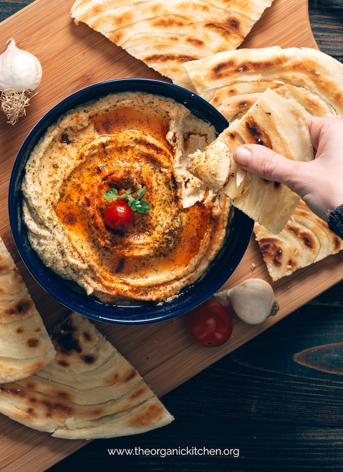 A hand holding pita after being dipped in Sun Dried Tomato Hummus!