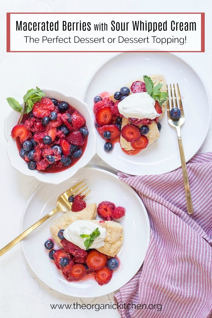 Two white plates with Macerated Berries and Sour Whipped Cream set on a white table