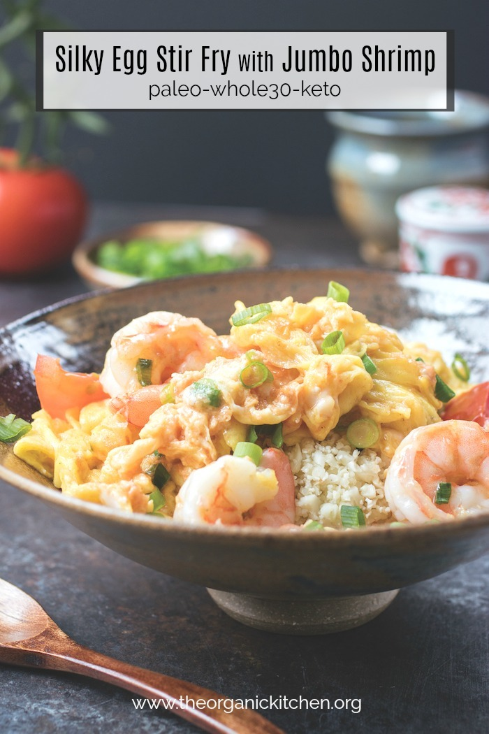 Silky Egg Stir Fry with Jumbo Shrimp in a gray bowl with tomatoes, onions and decorative jars in the background