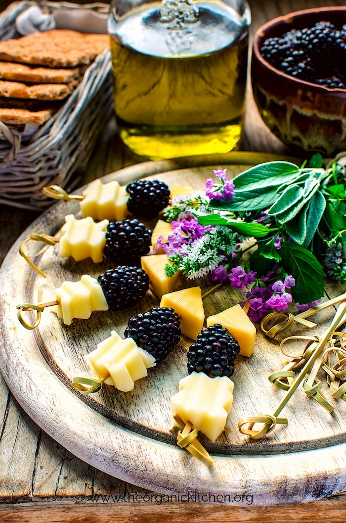 Blackberry and Aged Cheese Skewers on a serving board with baskets and bowls in the background filled with crackers and fruit