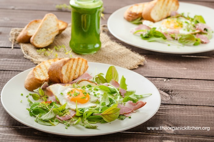 Two plates of Simple Green Salad with Ham and Fried Egg on white plates displayed on wooden table