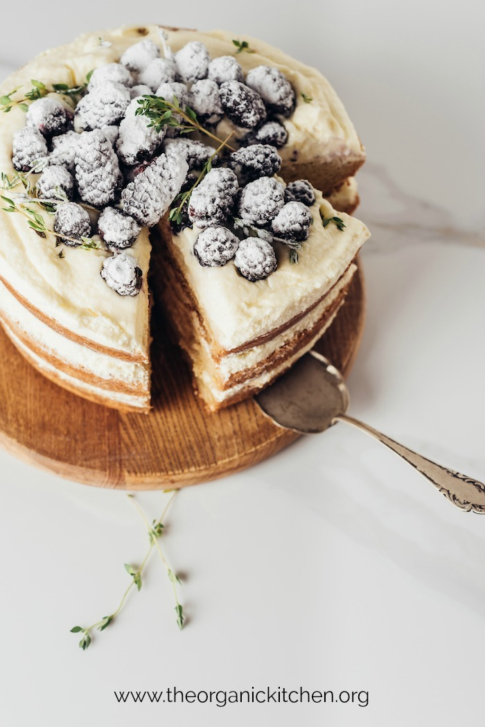 Triple layer Lemon Layer Cake with Blackberries on wooden cake plate with silver serving spatula