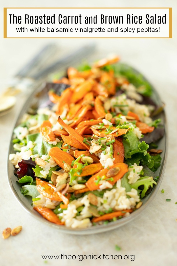 Roasted Carrot and Brown Rice Salad on a gray platter with serving spoons in the background