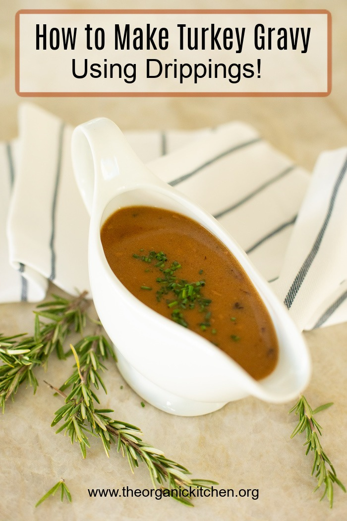 A gravy boat full of rich brown gravy surrounded by rosemary sprigs: How to Make Turkey Gravy with Drippings