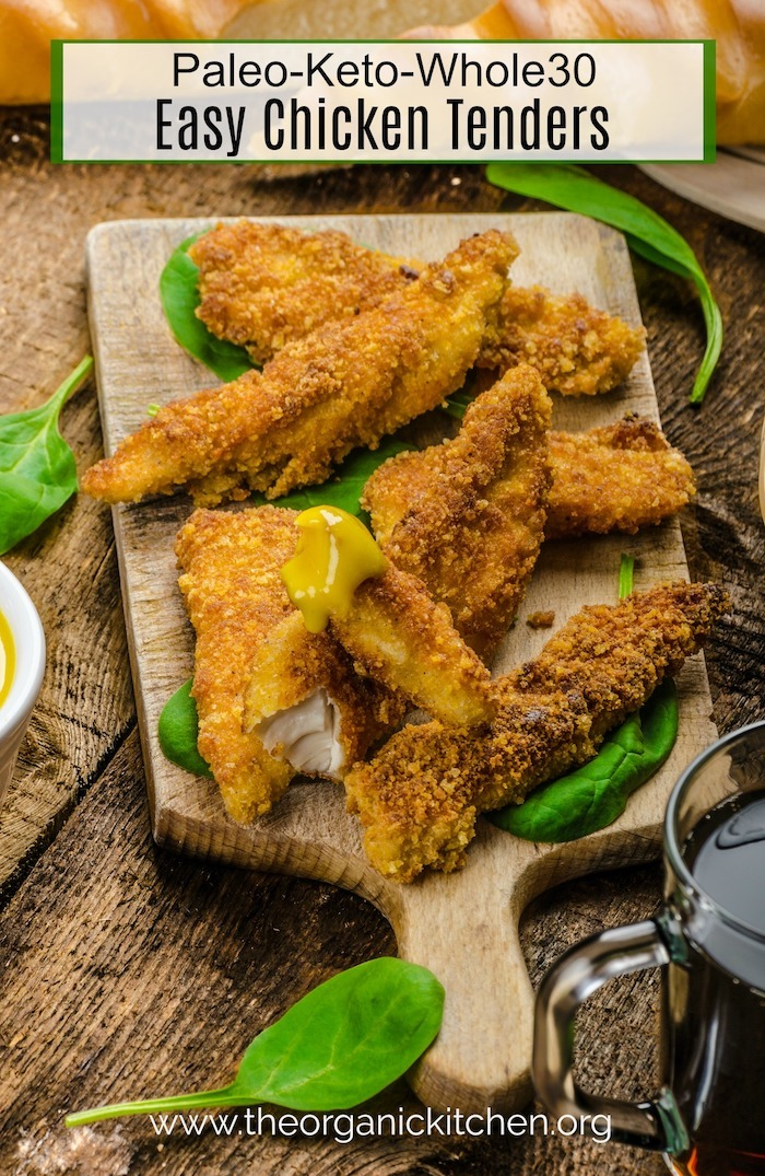 Keto-Paleo-Whole30 Easy Chicken Tenders on wooden cutting board garnished with greens