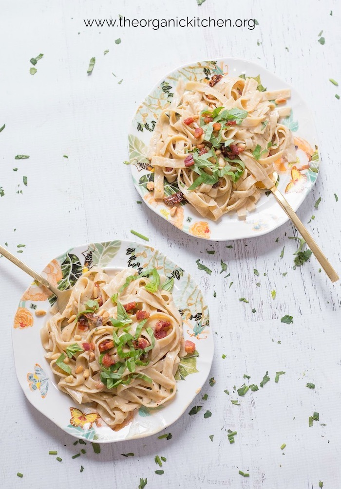 Two plates of Simple Fettuccine Alfredo with gold forks on white wood