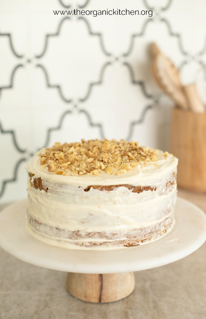 Carrot Cake with Cream Cheese Frosting garnished with chopped walnuts on cake plate