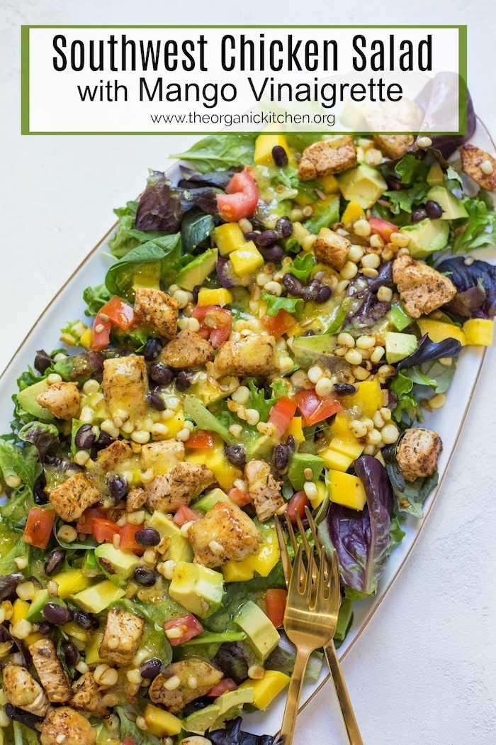 A close of of a platter with Southwest Chicken Salad with mango Vinaigrette with two gold forks