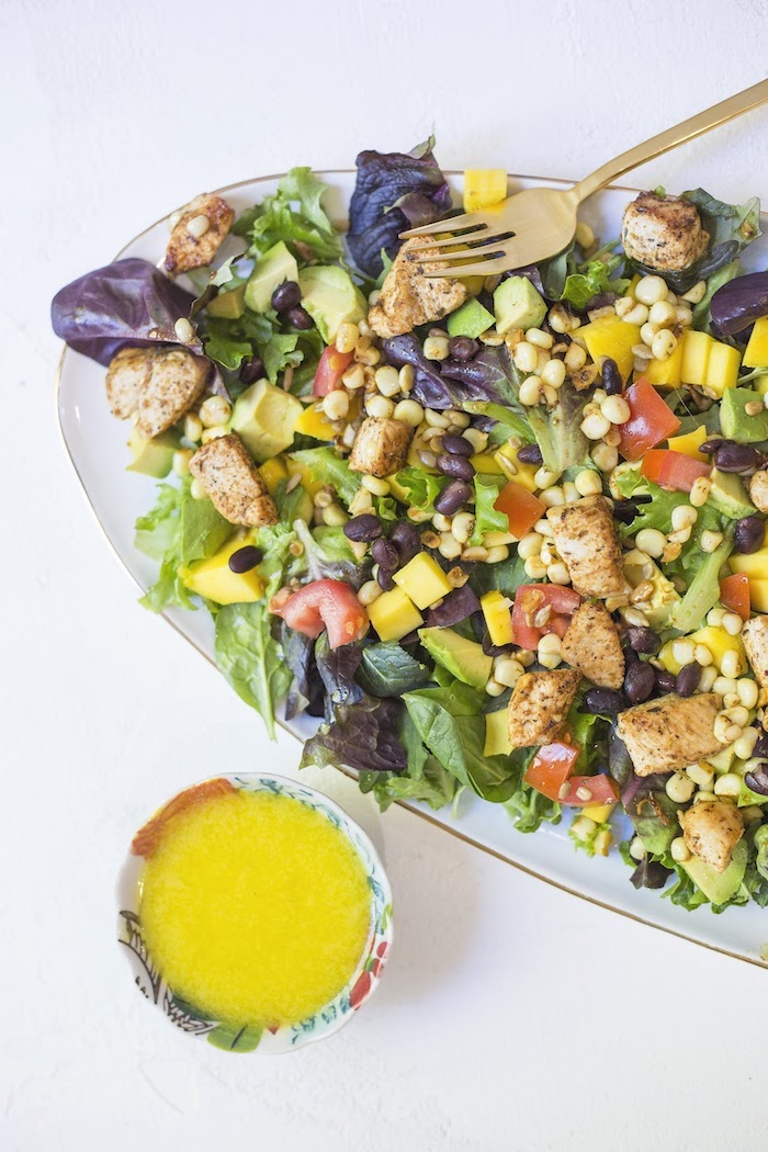 A vertical photo showing Southwest Chicken Salad with Mango Vinaigrette on a light blue platter with a colorful small bowl of bright yellow salad dressing