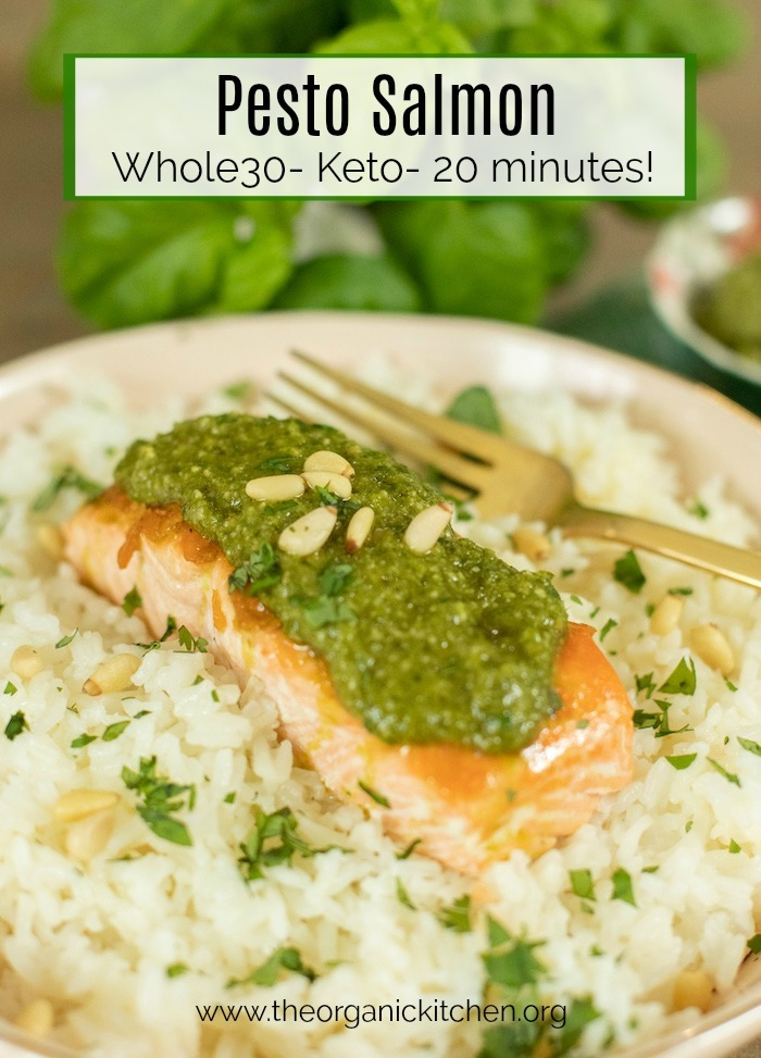 A single piece of of Pesto Salmon placed atop rice in a light pink dish with a gold fork