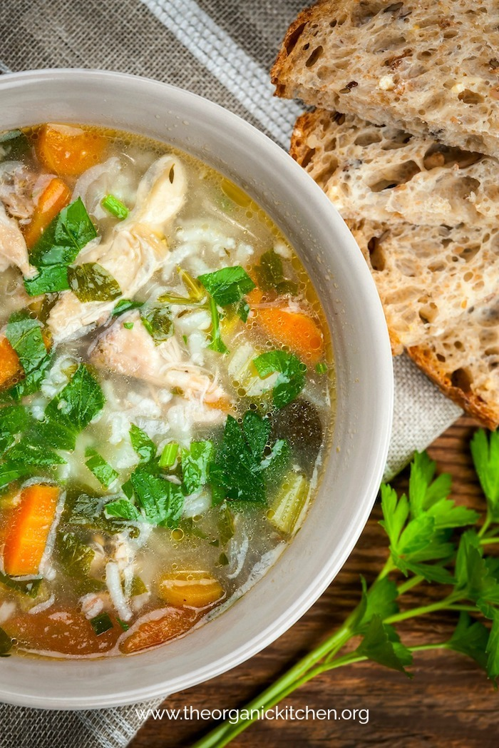 Chicken and rice soup with vegetables in bowl and bread from above with bread and parsley on wood table