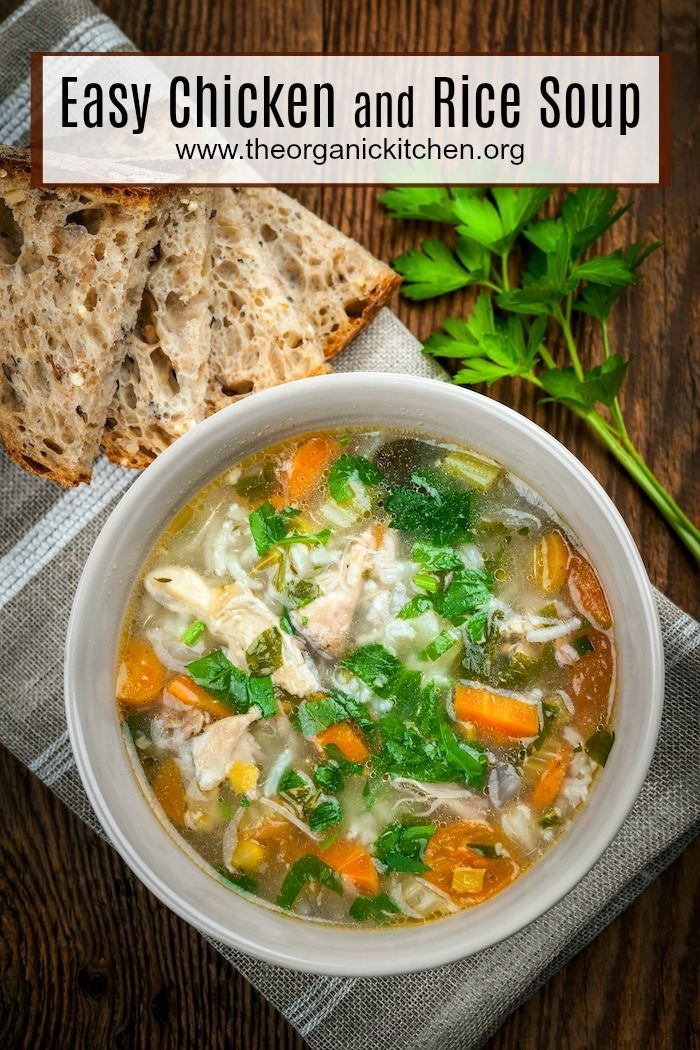 A white bowl of Easy Chicken and Rice Soup on a wooden table with three slices of bread