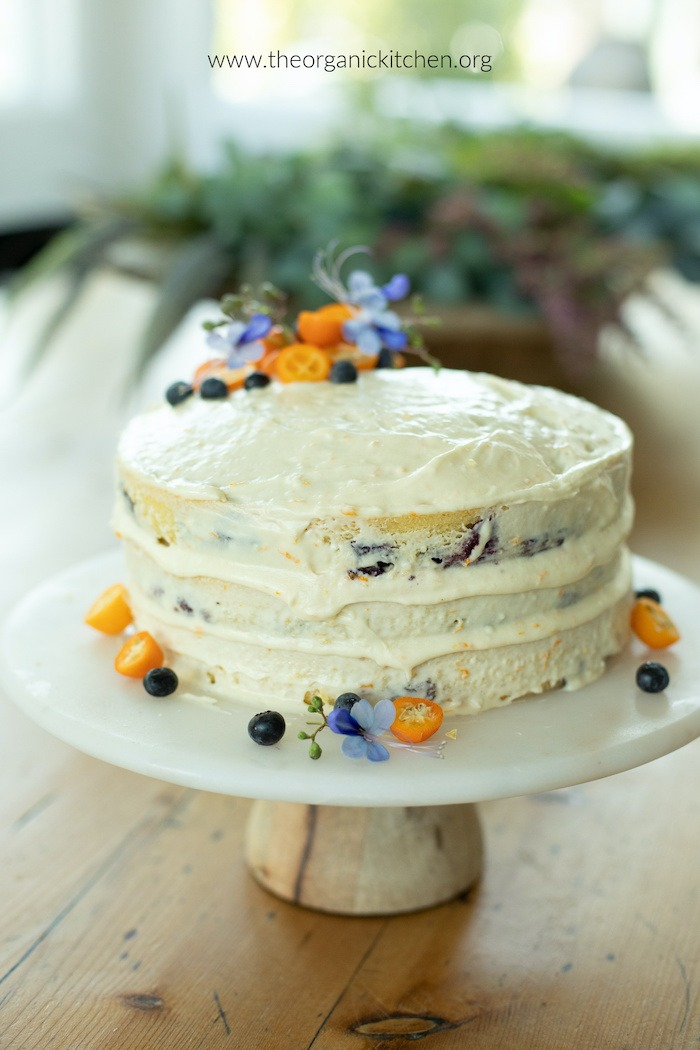 Orange Blueberry Cake with Orange Buttercream Frosting decorated with fruit and flowers on a white cake plate set on a table