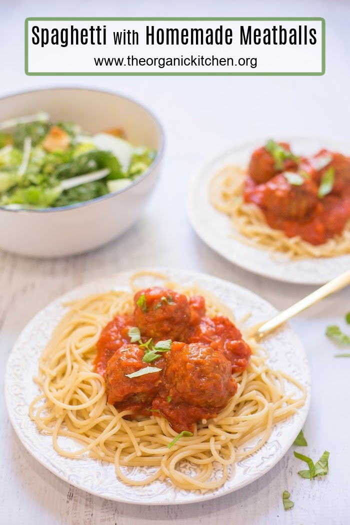 Spaghetti with Homemade Meatballs on two white plates with a bowl of Caesar salad