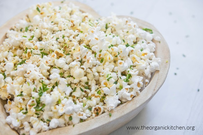 Parmesan Chive Popcorn in a wooden bowl on white surface