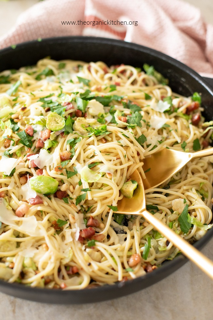 Pasta with Brussels Sprouts and Pancetta in black skillet with gold serving spoons
