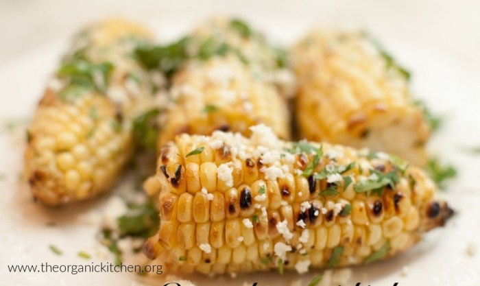 Four cobs of Mexican Street Corn on white surface