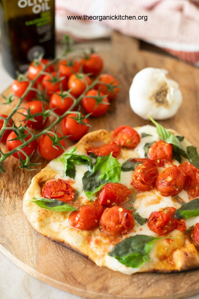 A freshly baked Grilled Naan Margherita Pizza on a wooden serving board