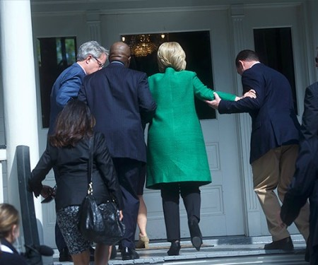 Hillary being helped up the stairs