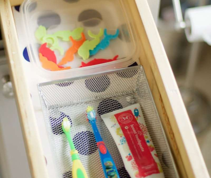 Kids' toothbrushes, toothpaste, and floss stored in small drawer with patterned liner. #bathroomorganization