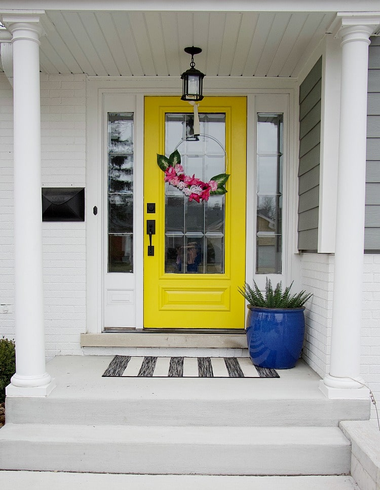 yellow front door with faux flower hoop wreath. Using items found from the Dollar Store, you can create a faux flower hoop wreath in this easy-to-follow tutorial with lots of pictures to help you create this spring trend! #fauxflowers #dollarstore #hoopwreath