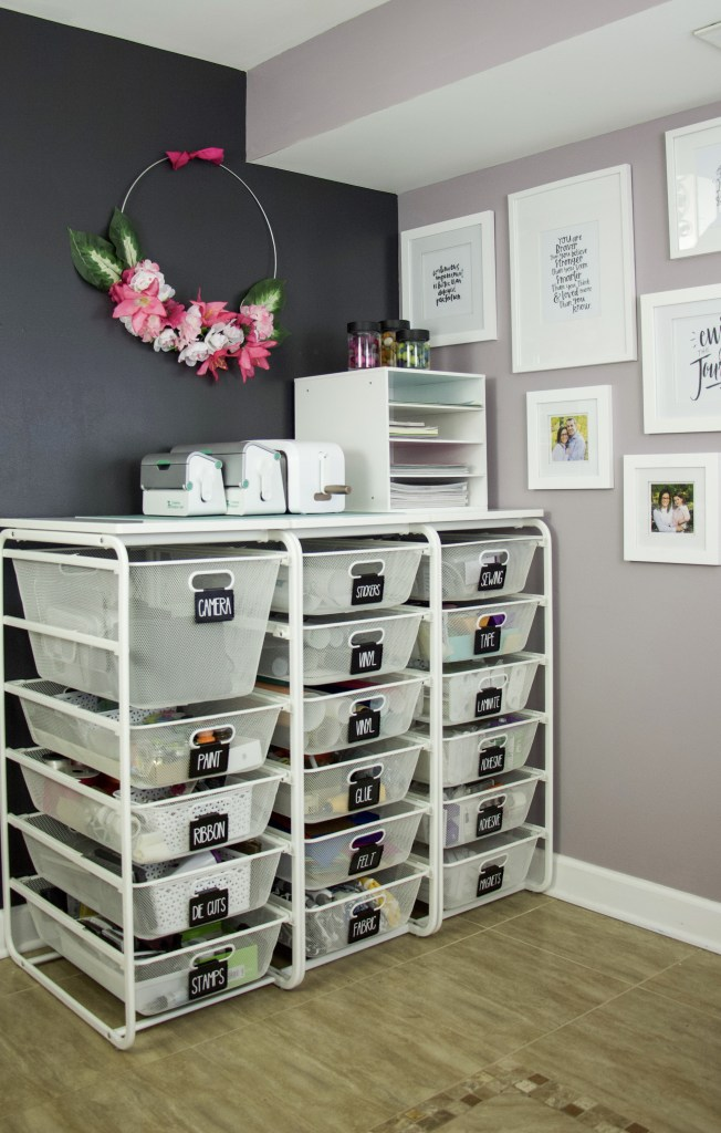Organize your home offiec with Elfa drawers and labels on each drawer. Categorize each drawer and label so you know what is inside. Elfa system against black wall and purple wall with wall art to create a beautiful and organized space #organized #craftorganization
