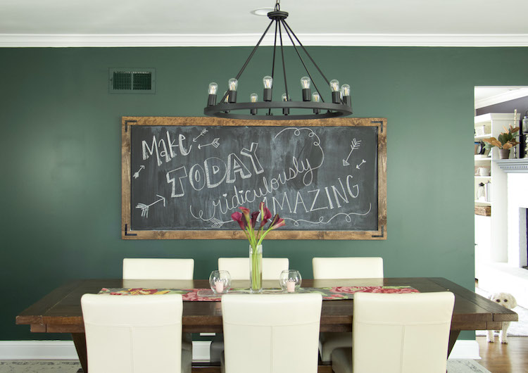 DIY chalkboard on moody dark green walls with black lighting and dining table to create a modern farmhouse vibe. #kitchendecor #modernfarmhouse #DIY