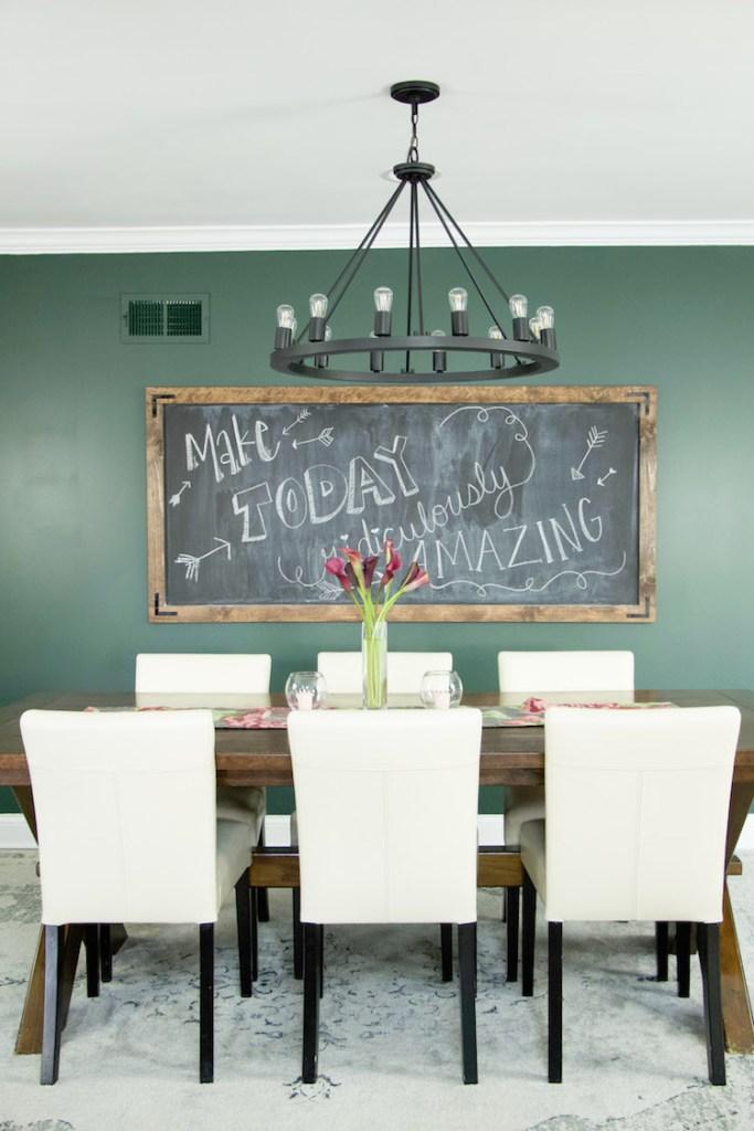 Dining room set against moody green kitchen walls dark paint color, black lighting, and DIY chalkboard. #modernfarmhouse #farmhousedecor #kitchen