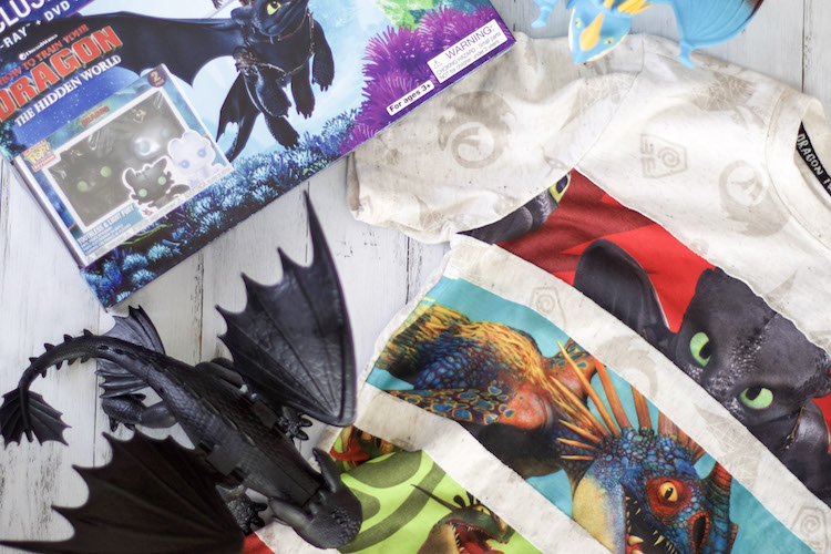Flatlay of How To Train Your Dragon 3 movie box set with action figure dragons and t-shirt