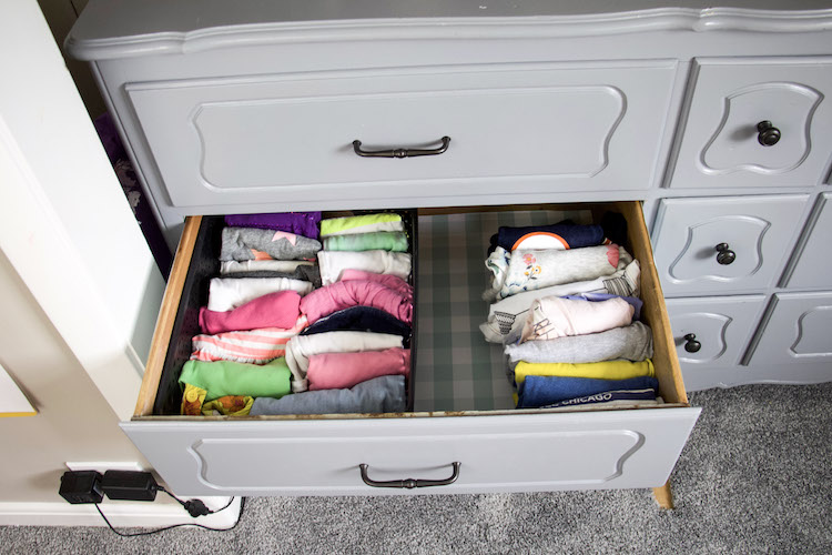 inside of a drawer with gingham drawer liner and clothing divided into t-shirts on right and tank tops on left in a container
