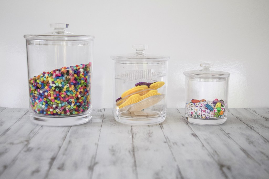 3 different size canisters that are all acrylic so you can see inside. One is full of pearler beads, one is pearler bead patterns, and one is pony beads. #organized