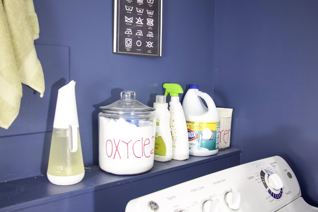 shelf with laundry detergents and glass jars to showcase how to create laundry room storage in a small laundry room