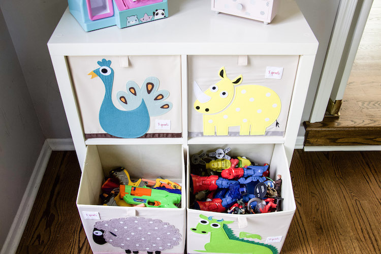 Cube organization of toys in playroom with bottom two drawers open displaying Nerf guns and action figures inside the cube organizers #playroom