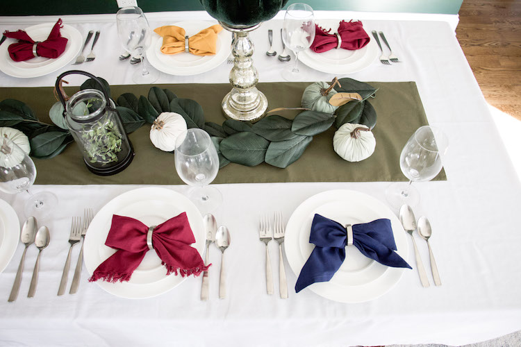 thanksgiving table decor with bow tie napkins set on white china