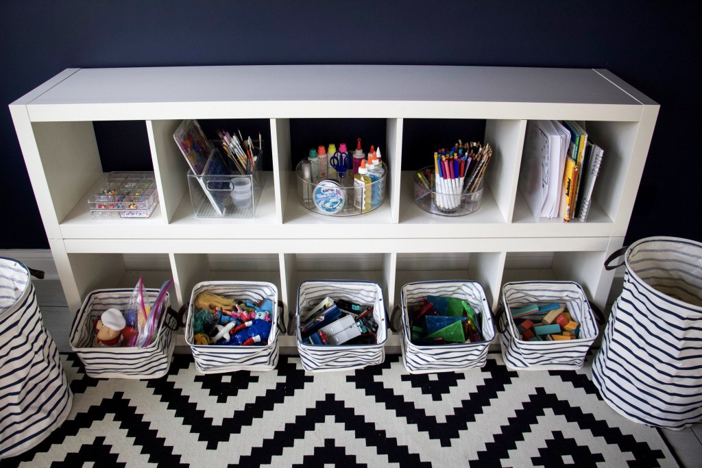 Organized shelves in playroom to represent skills to help kids get organized #organizedkids