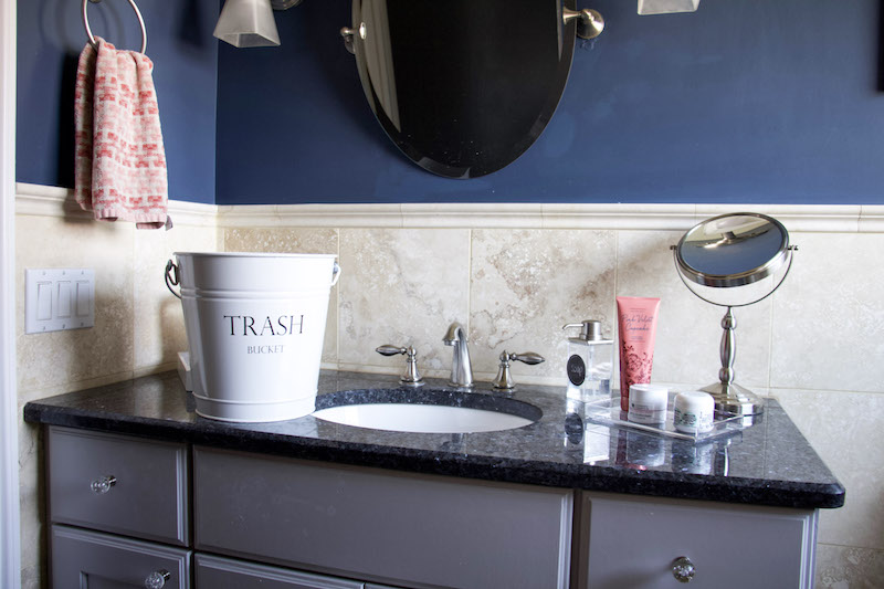 waste bucket on vanity with tray to organize counters