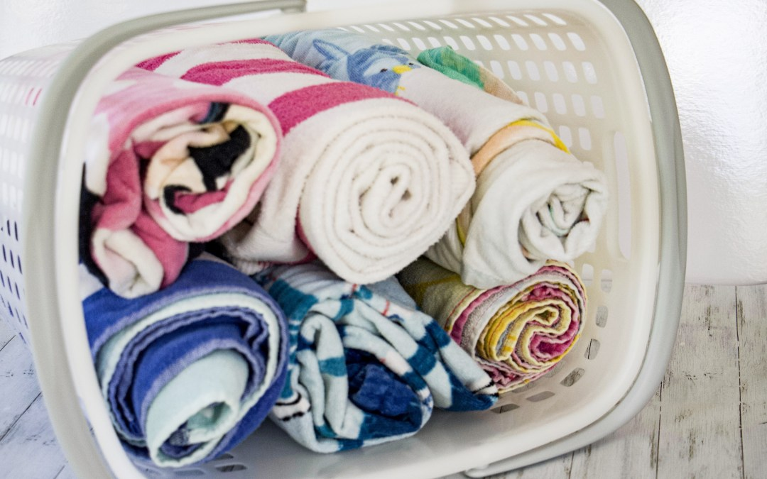 Beach towels rolled up in a basket to represent how to get organized for summer #summer